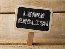 Bord op houten achtergrond met het Leren van Engelse woorden Stock Fotografie