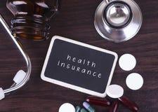 Bord, pillen en fles met stethoscoop, ziektekostenverzekeringwoord op houten lijst met copyspacegebied Royalty-vrije Stock Foto