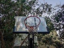 Borda da estrutura do basquetebol em um campo de jogos exterior cercado por árvores em um parque imagem de stock