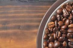 Borda de uns pires com feijões de café em uma placa de madeira Fotografia de Stock