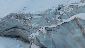 Borda do close-up da vista aérea de uma geleira de fluxo coberta com a neve e das pedras altas nas montanhas Destruição natural filme