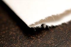 Borda do close-up do papel em uma tabela de madeira foto de stock