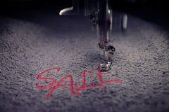 bordado de la VENTA roja de las letras en tela gris suave con la máquina del bordado - vista delantera detallada con humor ligero Fotos de archivo