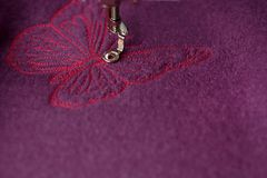 Bordado detallado de la mariposa rosada en las lanas hervidas púrpuras con una máquina del bordado fotos de archivo libres de regalías