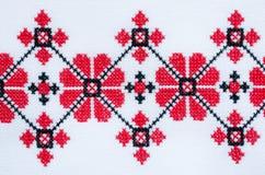 Bordado hecho a mano del elemento en el lino blanco por los hilos rojos y negros del algodón fotos de archivo libres de regalías