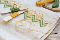 Bordado ucraniano en el bordado de lino de la tela y del hilo en una tabla de madera Imagen de archivo libre de regalías