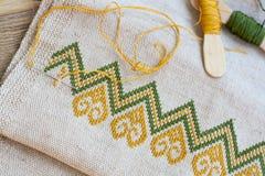 Bordado ucraniano en el bordado de lino de la tela y del hilo en una tabla de madera Foto de archivo libre de regalías
