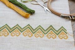 Bordado ucraniano en el bordado de lino de la tela y del hilo en una tabla de madera Imagen de archivo