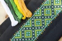 Bordado ucraniano en el bordado negro de la tela y del hilo en una tabla de madera ligera Foto de archivo