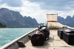 Bordadura do barco pela água azul e pela montanha azul Imagem de Stock