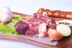 Bordas da carne, folha da alface, alho, moedor de pimenta e especiarias crus na mesa de madeira no fundo branco de cima de Imagens de Stock Royalty Free