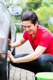 Bordas do carro da limpeza do homem com esponja Fotos de Stock Royalty Free