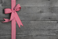 与红色和白色方格的弓的灰色木背景作为borde 免版税库存照片