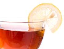 Borde de la taza transparente con té y el limón Imagen de archivo