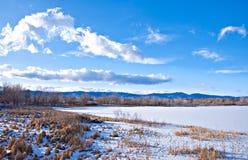 Borde de un lago congelado con la vista de montañas imagen de archivo libre de regalías