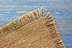 Borde del paño de la arpillera en una tabla azul Foto de archivo libre de regalías