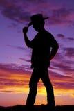 Borde del tacto del sombrero de vaquero del hombre de la silueta Fotografía de archivo libre de regalías