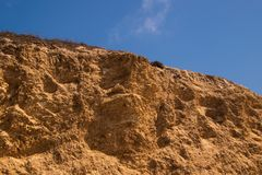 Borde marrón dentado rugoso del acantilado Hay un fondo profundo del cielo azul con la nube hinchada quebrada fotografía de archivo