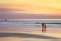 Borde que camina de los pares jovenes románticos de la playa del mar en la puesta del sol Imagenes de archivo