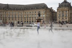 Bordeaux, Aquitaine / France - 06 10 2018 : girl dancing and splashing the water mirror in place de la bourse at Bordeaux, Stock Image