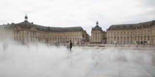 Bordeaux Aquitaine/Frankrike - 06 10 2018: gyckel för kvinnaflickalek i spegelspringbrunn framme av stället de la Börs i Bordeaux Royaltyfri Foto