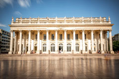 Bordeaux city in France. View on the facade of Grand Theatre building in Bordeaux city, France. Long exposure image technic with motion blurred people and clouds royalty free stock image