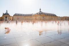 Bordeaux city in France. View on the famous Bourse square with mirror fountain in Bordeaux, France. Long exposure image technic with motion blurred people royalty free stock photography