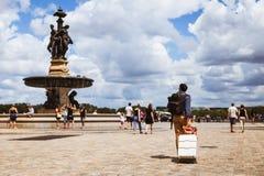 Tourist carrying luggage through Place de la Bourse, Bordeaux. Bordeaux, France - July 22 2018: Tourist crosses the Place de la Bourse carrying his luggage Royalty Free Stock Photo