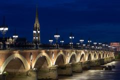 BORDEAUX, FRANCE - View of the Pont de pierre in the famous winery region Bordeaux, France. Tourists passing by stock photography