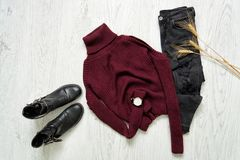 Bordeaux turtleneck, black boots, watches and ripped jeans. Spik Royalty Free Stock Photography