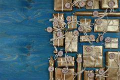 Advent calendar with 24 golden presents on teal. Border of advent calendar with twenty four golden presents on teal wood with negative space to the left Stock Photos