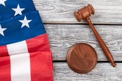 Border from American flag and wooden gavel. Justice gavel and folded flag of America on rustic wooden boards, top view Stock Photo