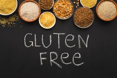 Various gluten free groats on black background with copy space. Border of assorted gluten free grains in bowls on black background, copy space, top view, chalk royalty free stock images