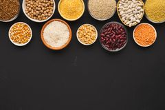 Various gluten free groats on black background with copy space. Border of assorted gluten free grains in bowls on black background, copy space, top view royalty free stock images