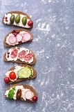 The border is assorted from a variety of bruschetta on a gray background. Bruschetta with sausage and vegetables. Top view, copy s royalty free stock photo
