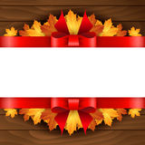 Border of autumn maples leaves decorated with a red bow  Royalty Free Stock Photo
