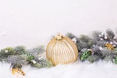 Border from ball, golden and green pine cones and branches fir tree near by white textured wall. Decorative christmas composition. Selective focus. Place for royalty free stock photos