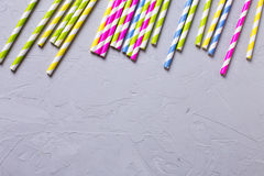 Border from bright  paper straws on textured background. Stock Photos