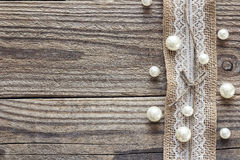 Border of burlap with white lace and beads on old wooden table. Design for border or background. Place for text, top view stock images