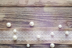 Border of burlap with white lace and beads on old wooden table. Design for border or background. Place for text, top view royalty free stock images