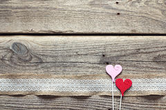 Border of burlap with white lace and decorative hearts on old wooden table. Design for border or background. Place for text. royalty free stock photo