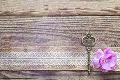 Border of burlap with white lace, vintage key and purple flower. On old wooden table. Design for border or background. Place for text, top view stock images