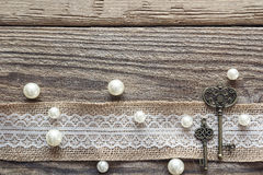 Border of burlap with white lace, vintage keys and beads on old. Wooden table. Design for border or background. Place for text, top view royalty free stock images