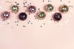 Border of Christmas decorations and copy space on a pink backgr. Ound. Composition of mirror ballss and sparkles stars. Top view, flat lay royalty free stock photography
