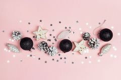 Border of Christmas decorations on a pink background. Compositi. On of cones, black balls, candles and stars. Top view, flat lay royalty free stock images