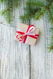 Border of Christmas gift boxes and fir tree branch on wooden table. Top view with copy space Royalty Free Stock Photos