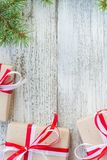 Border of Christmas gift boxes and fir tree branch on wooden table. Top view with copy space Royalty Free Stock Image