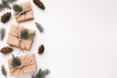 Border of christmas gifts and pine cones on white. Background stock image