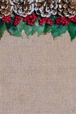 Border of Christmas pinecones, holly leaves and red berries on rustic burlap fabric background royalty free stock photography