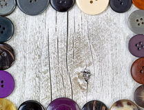 Border of clothing buttons on rustic white wood Royalty Free Stock Photos